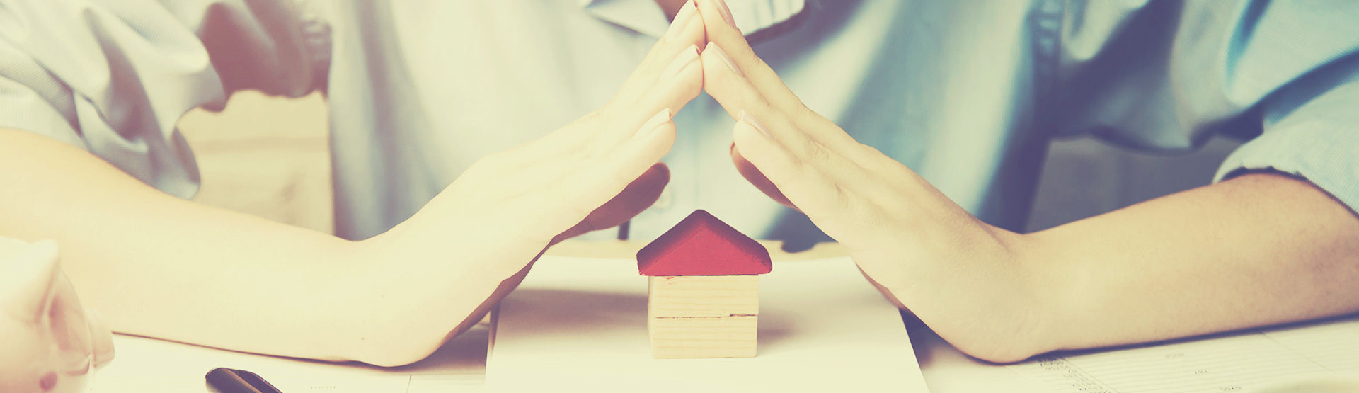 Hands over a tiny block house